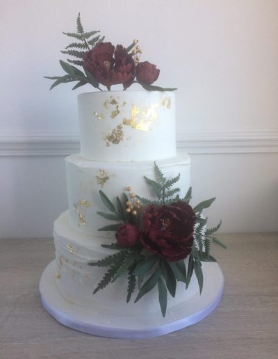 Rustic Wedding Cake with Burgnady and foliage accents